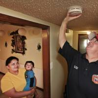 Photo - Leticia Pina her daughter Mateo, 8 months, watch Oklahoma City firefighters Major Sheila Hays installs a new smoke alarms in their northwest Oklahoma City home, Tuesday, October 1, 2013.  Photo by David McDaniel, The Oklahoman