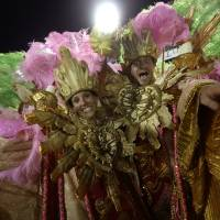 Photo - U.S. citizen Paul Leaury, right, and an unidentified fellow foreign member of the Mangueira samba school, dance during a carnival parade at the Sambadrome in Rio de Janeiro, Brazil, Tuesday, Feb. 12, 2013. While non-Brazilians have long shelled out hundreds of dollars for the right to dress up in over-the-top costumes and boogie in Rio's samba school parades, which wrapped up Monday in an all-night extravaganza, few in the so-called