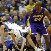 Photo - Minnesota Timberwolves' Ricky Rubio left, of Spain, falls to the floor after a called charge on Los Angeles Lakers' Kobe Bryant in the first quarter of an NBA basketball game Friday, Feb. 1, 2013, in Minneapolis. (AP Photo/Jim Mone)