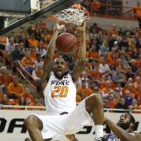 Photo - Oklahoma State forward Michael Cobbins (20) dunks in front of Kansas State guard Rodney McGruder, back left, and forward Thomas Gipson (42) in the first half of an NCAA college basketball game in Stillwater, Okla., Saturday, March 9, 2013. (AP Photo/Sue Ogrocki)