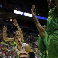 Photo - Wisconsin guard Traevon Jackson (12) drives to the basket against Oregon defense during the second half of a third-round game of the NCAA college basketball tournament Saturday, March 22, 2014, in Milwaukee. (AP Photo/Morry Gash)