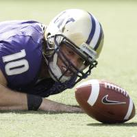 Photo - University of Washington quarterback Jake Locker eyes the ball after he fumbled in the second quarter of an NCAA college football game against BYU Saturday, Sept. 6, 2008, at Husky Stadium in Seattle. Washington tight end Kavario Middleton recovered the ball on the play, but BYU beat Washington 28-27. (AP Photo/Ted S. Warren) ORG XMIT: WATW106