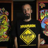 Photo -   In this photo taken April 30, 2012, Dave Snell of New Zealand stands in front of what he calls bogan art in Hamilton, New Zealand. Snell graduated from Waikato University in Hamilton on Thursday, May 3, 2012, with a doctoral degree that examined the social habits of headbangers - heavy-metal music fans that are known as