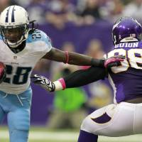 Photo -   Tennessee Titans running back Chris Johnson, left, tries to break a tackle by Minnesota Vikings defensive tackle Letroy Guion during the first half of an NFL football game on Sunday, Oct. 7, 2012, in Minneapolis. (AP Photo/Genevieve Ross)