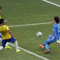 Photo - Mexico's goalkeeper Guillermo Ochoa, right, deflects a ball as Brazil's David Luiz, left, and  Paulinho approach during the group A World Cup soccer match between Brazil and Mexico at the Arena Castelao in Fortaleza, Brazil, Tuesday, June 17, 2014.  (AP Photo/Themba Hadebe)