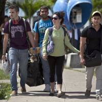 """Photo - HOLD FOR RELEASE AT 12:01 A.M., EDT ON MONDAY, AUG. 4, 2014 - In this July 11, 2014, photo, Cuban students exit Marta Abreu Central University in Santa Clara, Cuba. Beginning as early as October 2009, a project overseen by the U.S. Agency for International Development sent Venezuelan, Costa Rican and Peruvian nationals to Cuba to cultivate a new generation of political activists. Often posing as tourists, the young travelers befriended Cuban students. Fernando Murillo, contracted to turn politically apathetic young Cubans into """"change agents,"""" headed to Santa Clara and connected with a cultural group that called itself """"Revolution,"""" a modest outfit of street artists devoted to electronic music and video. (AP Photo/Franklin Reyes)"""