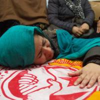 Photo - A relative of slain opposition leader Chokri Belaid cries over his coffin at his parents' home near Tunis, Thursday, Feb. 7, 2013. The Islamist party dominating Tunisia's ruling coalition on Thursday rejected its own prime minister's decision to form a non-partisan technocratic government to try to appease critics, signaling that the political crisis brought on by the assassination of Belaid, a prominent leftist politician, is far from over. (AP Photo/Amine Landoulsi)