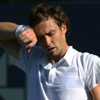 Photo - Ernests Gulbis, of Latvia, wipes sweat from his brow between points against Dominic Thiem, of Austria, during the second round of the 2014 U.S. Open tennis tournament, Friday, Aug. 29, 2014, in New York. (AP Photo/John Minchillo)