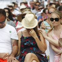 Photo -   Australian relatives of the victims of the 2002 Bali bombings comfort each other during a memorial service, marking the 10th anniversary of the terrorist attacks at nightclubs in Kuta that killed 202 people, including 88 Australians and seven Americans, in Jimbaran in Bali, Indonesia, Friday, Oct. 12, 2012. (AP Photo/Made Nagi, Pool)
