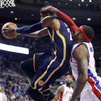 Photo - Indiana Pacers forward Paul George (24) goes to the basket past Detroit Pistons forward Josh Smith (6) during the first half of an NBA basketball game Saturday, March 15, 2014, in Detroit. (AP Photo/Duane Burleson)