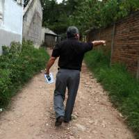 Photo -   In this photo taken on Wednesday, Oct 17, 2012, Wilfredo Yanez, points at a bullet mark on a wall at the site where his late son Jaasiel Yanez, 15, was shot dead allegedly by soldiers in Tegucigalpa, Honduras. According to his relatives, Jaasiel was killed by soldiers early Sunday, May 27, when he was riding a motorcycle, near a military checkpoint, allegedly accompanied by a young woman. (AP Photo/Esteban Felix)