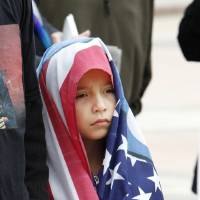 Photo - Left: Destiny Williamson, 8, of Midwest City, listens Friday to speakers from Idle No More.