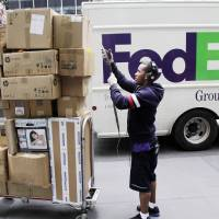 Photo -   In this Friday, May 11, 2012, file photo, a FedEx worker sorts boxes for delivery as they are unloaded from a FedEx truck in New York. FedEx Corp. said Tuesday, June 19, 2012, that slow global growth will crimp its earnings results over the next 12 months, but it's vowing to make significant cost cuts to make up for any shortfall.(AP Photo/Mark Lennihan)