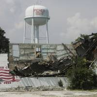 Photo - DAMAGE: In this photo taken Wednesday, July 8, 2009, the Picher, Oka. water tower is seen behind a building damaged by a lightning strike and subsequent fire in Picher, Okla. (AP Photo/Sue Ogrocki) ORG XMIT: OKSO109