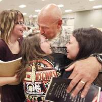 Photo - Lt. Col. Bruce Arnold gets hugs from his three daughters, Samantha (left), Kiersten and Kaitlin, as the Oklahoma National Guard welcomes 64 members of the 2-45th Agri-business Development Team home from a 10-month deployment to Afghanistan, during a ceremony Saturday afternoon at the Norman Armed Forces Reserve Center. By Paul Hellstern, The Oklahoman ORG XMIT: KOD  PAUL HELLSTERN