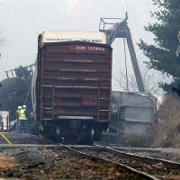 Photo - Officials stand next to derailed freight train cars in Paulsboro, N.J., Friday, Nov. 30, 2012, after several tanker cars carrying hazardous materials toppled from a bridge and into a creek. At least one tanker car may contain vinyl chloride, Gloucester County Emergency Management director J. Thomas Butts told WPVI-TV. (AP Photo/Mel Evans)
