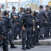 Photo - Police guard the streets near the Maracana stadium before the game between Argentina and Bosnia during the 2014 soccer World Cup in Rio de Janeiro, Brazil, Sunday, June 15, 2014. (AP Photo/Silvia Izquierdo)