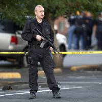 Photo - A SWAT team officer stands watch near an apartment house where the suspect in a shooting at a movie theatre lived in Aurora, Colo., Friday, July 20, 2012. As many as 14 people were killed and 50 injured at a shooting at the Century 16 movie theatre early Friday during the showing of the latest Batman movie. (AP Photo/Ed Andrieski) ORG XMIT: COEA108
