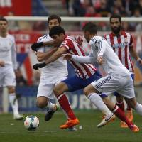 Photo - Atletico's Diego Costa, center, in action with Real's Xabi Alonso, left, during a Spanish La Liga soccer match between Atletico de Madrid and Real Madrid at the Vicente Calderon stadium in Madrid, Spain, Sunday, March 2, 2014. (AP Photo/Gabriel Pecot)