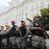 Photo - National Force police officers stand guard outside the Copacabana Palace where Ray Whelan, of MATCH Services, is staying, in Rio de Janeiro, Brazil, Tuesday, July 8, 2014.  The World Cup corporate hospitality executive was arrested at the Copacabana Palace, the hotel used by FIFA officials during the World Cup. Whelan, who is suspected of involvement with a ticket-scalping ring, was released from prison early Tuesday. (AP Photo/Leo Correa)
