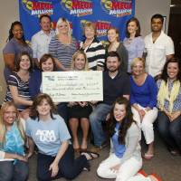 Photo - Employees from Urban Dealight gather for a photo with a big check Wednesday at the Oklahoma Lottery Commission after their office pool won $10,003 in the Mega Millions drawing last week.  Photo by Doug Hoke, The Oklahoman