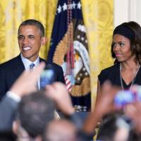 Photo - President Barack Obama, left, with first lady Michelle Obama, speaks during a reception to observe LGBT Pride Month in the East Room of the White House in Washington, Monday, June 30, 2014.    (AP Photo/Manuel Balce Ceneta)