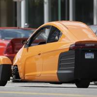 Photo - The Elio, a three-wheeled prototype vehicle, is shown in traffic in Royal Oak, Mich., Thursday, Aug. 14, 2014. Instead of spending $20,000 on a new car, Paul Elio is offering commuters a cheaper option to drive to work. His three-wheeled vehicle The Elio will sell for $6,800 car and can save on gas with fuel economy of 84 mpg. (AP Photo/Paul Sancya)