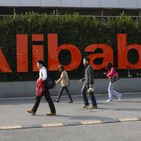 Photo - FILE - In this March 17, 2014 file photo, people walk past a company logo at the headquarters of Alibaba Group in Hangzhou, in eastern China's Zhejiang province. Alibaba is pulling back the curtain a little bit more Monday, June 16, 2014, providing more information about its partnership structure and financials ahead of its planned initial public offering. (AP Photo)  CHINA OUT