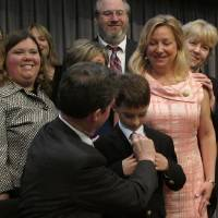 Photo - Kansas Gov. Sam Brownback adjusts 8-year-old Brad Eckart's tie before taking a group photo with parents of children with autism who supported a new law requiring limited health insurance coverage for treatment, Wednesday, April 16, 2014, in Overland Park. Brad's mother, to his right, Heidi Eckart, estimates the family has spent $500,000 on treating him. (AP Photo/John Hanna)