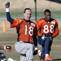 Photo - Denver Broncos quarterback Peyton Manning (18) stretches with wide receiver Demaryius Thomas (88) during NFL football practice at the team's training facility in Englewood, Colo., Saturday, Jan. 25, 2014. The Broncos are scheduled to play the Seattle Seahawks in Super Bowl XLVIII on Feb. 2. (AP Photo/Ed Andrieski)
