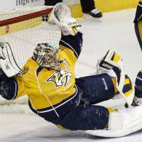 Photo - Nashville Predators goalie Pekka Rinne, of Finland, makes a stop against the Pittsburgh Penguins in the first period of an NHL hockey game Tuesday, March 4, 2014, in Nashville, Tenn. (AP Photo/Mark Humphrey)
