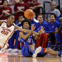 Photo - Oklahoma forward Amath M'Baye (22) reaches for the ball as Kansas forward Kevin Young passes it during the first half of an NCAA college basketball game in Norman, Okla., Saturday, Feb. 9, 2013. (AP Photo/Sue Ogrocki) ORG XMIT: OKSO101