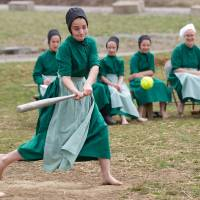 Photo - Amish girls play softball after class during an end of the school year celebration on Tuesday, April 9, 2013 in Bergholz, Ohio.  The celebration was also part of a farewell picnic for those sentenced in the hair and beard cutting scandal earlier in the year. (AP Photo/Scott R. Galvin)