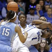 Photo - North Carolina's Allisha Gray (15) and Stephanie Mavunga guard Duke's Elizabeth Williams (1) during the second half of an NCAA college basketball game in Durham, N.C., Monday, Feb. 10, 2014. North Carolina won 89-78. (AP Photo/Gerry Broome)