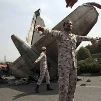 Photo - Iranian Revolutionary Guards prevent the media from approaching the wreckage of a passenger plane crash near the capital Tehran, Iran, Sunday, Aug. 10, 2014. An Iranian passenger plane crashed Sunday while taking off from an airport near the capital, Tehran, killing tens of people onboard, state media reported. (AP Photo/Vahid Salemi)