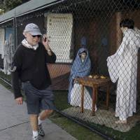 Photo -   FILE - In this Dec. 13, 2011 file photo, a man walks past two of the traditional Nativity scenes along Ocean Avenue at Palisades Park in Santa Monica, Calif. Avowed atheist Damon Vix last year won two-thirds of the booths in the annual, city-sponsored lottery to divvy up spaces in the live-sized Nativity display. But he only put up one thing: A sign that read