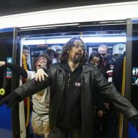 Photo - People dressed and made up as Zombies get off a metro train during the annual Zombie march in Madrid, Saturday Feb. 27, 2010. The zombie march is in homage by fans to the Zombie film genre and to U.S. director George A. Romero, famous for his Zombie horror movies. (AP Photo/Paul White)
