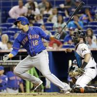 Photo - New York Mets' Juan Lagares (12) watches after hitting a RBI singe to score Wilmer Flores in the fourth inning during a baseball game, Tuesday, Sept. 2, 2014, in Miami. At right is Miami Marlins catcher Jarrod Saltalamacchia. (AP Photo/Lynne Sladky)