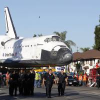 Photo -   The Space Shuttle Endeavour is slowly moved down Martin Luther King Blvd. in Los Angeles Sunday, Oct. 14, 2012. In thousands of Earth orbits, the space shuttle Endeavour traveled 123 million miles. But the last few miles of its final journey are proving hard to get through. Endeavour's 12-mile crawl across Los Angeles to the California Science Museum hit repeated delays Saturday, leaving expectant crowds along city streets and at the destination slowly dwindling. Officials estimated the shuttle, originally expected to finish the trip early Saturday evening, would not arrive until later Sunday. (AP Photo/Alex Gallardo)