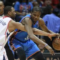Photo - Oklahoma City Thunder forward Kevin Durant (35) drives against Atlanta Hawks forward Tracy McGrady (1) in the the first half of an NBA basketball game Saturday, March 3, 2012, in Atlanta. (AP Photo/John Bazemore)  ORG XMIT: GAJB116