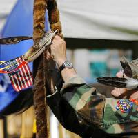 Photo -  U.S. Marine Corps veteran Jerry Best secures a small American flag and ribbons to a warrior's staff in front of a tent for the Oklahoma City VA Warriors Group. Photo by Jim Beckel, The Oklahoman   Jim Beckel -