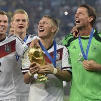 Photo - Germany's Bastian Schweinsteiger celebrates with the trophy after the World Cup final soccer match between Germany and Argentina at the Maracana Stadium in Rio de Janeiro, Brazil, Sunday, July 13, 2014. Germany won the match 1-0.   (AP Photo/Martin Meissner)