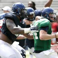 Photo - Mississippi defensive tackle Robert Nkemdiche, left, hauls down quarterback Bo Wallace during their final open NCAA college football practice, Saturday, Aug. 9, 2014, at Mississippi, in Oxford Miss. Players were involved in individual and team drills. (AP Photo/Rogelio V. Solis)