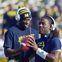 Photo -   Michigan quarterback Denard Robinson, right, handles a ball alongside quarterback Devin Gardner, back, during warmups before an NCAA college football game against Iowa, Saturday, Nov. 17, 2012, in Ann Arbor, Mich. Robinson has missed the past two games with nerve damage in his elbow. (AP Photo/Tony Ding)