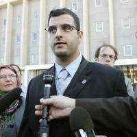 Photo - Muneer Awad talks Monday with reporters outside the Oklahoma City federal courthouse after a  judge extended a temporary restraining order over State Question 755.   PAUL HELLSTERN