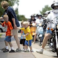 Photo - James Maguire, 6, Zack Maguire, 3 and Zane Zielny, 3, walk with Melissa Maguire into the zoo as the scooters arrive.