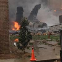 Photo -   The burning fuselage of an F/A-18 Hornet lies smoldering after crashing into a residential building in Virginia Beach, Va., Friday, April 6, 2012. The Navy did not immediately return telephone messages left by The Associated Press, but media reports indicate the two aviators were able to eject from the jet before it crashed. They were being treated for injuries that were not considered life threatening. (AP Photo)