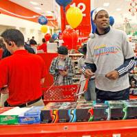 Photo -  Oklahoma City Thunder player Kevin Durants helps families check out of a target during a shopping spree with the Sunbeam Family Services Grandparents Raising Grandkids program and the Thunder in Oklahoma City, Thursday, December 16, 2010.  Photo by Bryan Terry, The Oklahoman