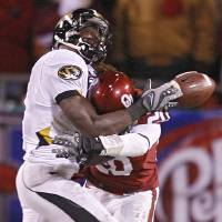 Photo - CELEBRATE / CELEBRATION: Oklahoma's Quinton Carter (20) breaks up a pass for Missouri's Jeremy Maclin (9) during the second half of the Big 12 Championship college football game between the University of Oklahoma Sooners (OU) and the University of Missouri Tigers (MU) on Saturday, Dec. 6, 2008, at Arrowhead Stadium in Kansas City, Mo.   PHOTO BY BRYAN TERRY, THE OKLAHOMAN  ORG XMIT: KOD