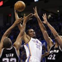 Photo -  Kevin Durant, center, goes over San Antonio's Boris Diaw, left, and Tim Duncan on Saturday night in Game 4. (Associated Press photo)